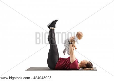 Mother laying on an exercise mat and lifting a baby girl isolated on white background