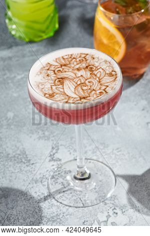 The Clover Club Cocktail is a cocktail consisting of gin, lemon juice, raspberry syrup, and egg white. Red Clover Club Cocktail with white foam and cinnamon powder. Vintage table,  sunshine and shadow