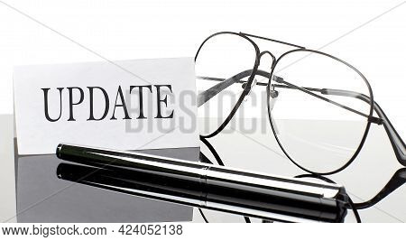 The Word Update Is Written In A White Notepad Near A Calculator, Coffee, Glasses And A Pen. Business