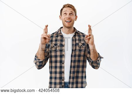 Hopeful Redhead Man Looking Up With Crossed Fingers, Praying Or Waiting For Miracle, Making Wish, An