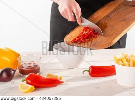 Hand Taking Cut Red Pepper Off The Wooden Board With A Knife