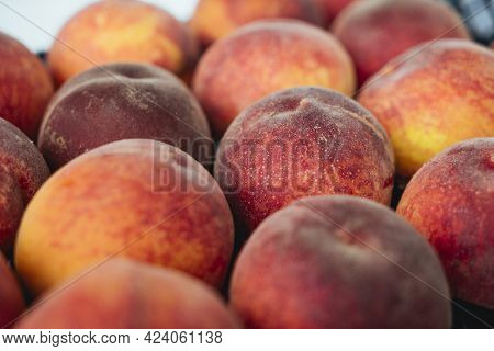 Peaches In A Black Box. Many Peaches On The Market. Box Full Of Fresh Picked Peaches. Close-up Of Co
