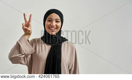 Happy Young Arabian Woman In Hijab Showing Victory Sign While Looking At Camera On Light Background
