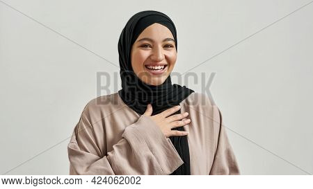 Portrait Of Laughing Young Arabic Woman In Hijab Looking At Camera And Smiling On Light Background,