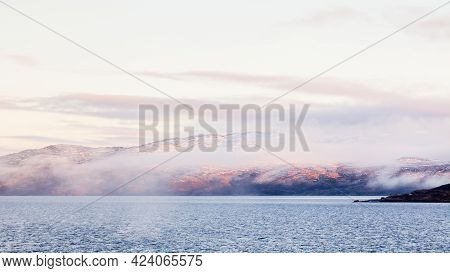 Norwegian Coastline.  A Winter View Of The Rocky Coastline Shrouded In Mist Close To The Norwegian T