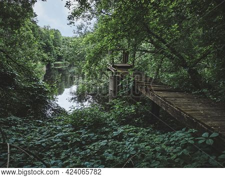 An Old Abandoned Pier By A Beautiful Lake In The Woods. Old Broken Wooden Bridge In The Reeds For Fi