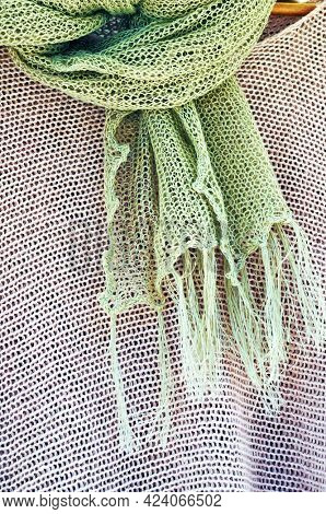 Linen knitted scarf and knitted blouse on hanger. Ladies' summer linen wear.