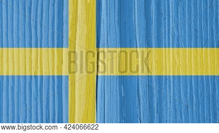 The Flag Of Sweden On A Dry Wooden Surface, Cracked With Age. It Seems To Flutter In The Wind. Patri