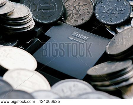 Japanese Money Coins And Enter Button Close-up. Coins In 1 Yen Lie On The Black Keyboard Of A Comput