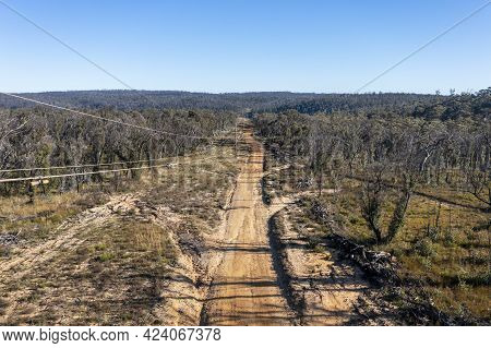 Drone Aerial Photograph Of Telephone Poles And Wires Along A Dirt Track After A Bushfire In A Forest