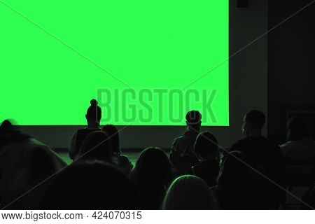 Audience Sits In A Dark Room. Demonstration Through A Presentation Or Movie Projector. Blank Screen,