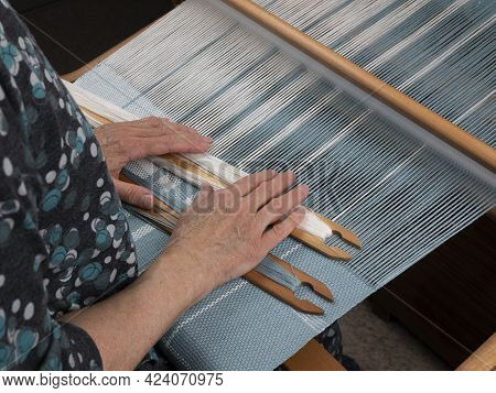 Artisan's Hands With Two Shuttles On The Hand Loom. Weaving Of The Fabric With Striped Pattern