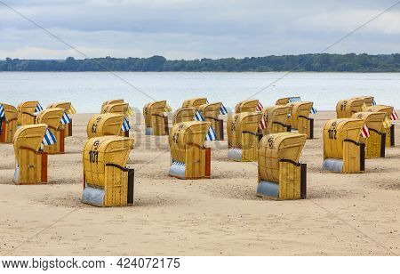 Colorful Wooden Hooded Beach Chairs (strandkorb) On A Sandy Baltic Beach In Travemunde Seaside Resor