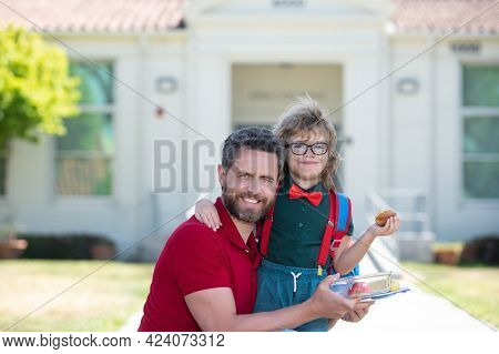 Father And Son Come Back From School. Little Schoolboy Eating Tasty Lunch Outdoors.