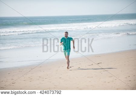Man Running On Beach. Jogging On A Sandy Beach Near Sea Or Ocean.