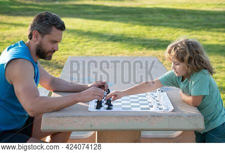 Father And Son Playing Chess Spending Time Together In Park. Child Playing Board Game With Parent. M