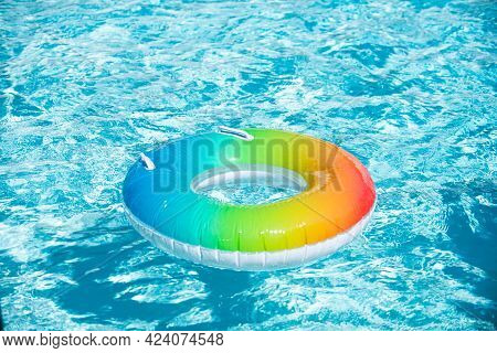 Inflatable Ring Floating In Pool On Summer Background. Rainbow Swimming Pool Ring Float In Blue Wate