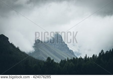 Dark Atmospheric Landscape With High Rocky Mountain Top Among Big Low Clouds. Dark Forest Silhouette
