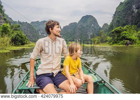 Dad And Son Tourists In Boat On The Lake Tam Coc, Ninh Binh, Viet Nam. Its Is Unesco World Heritage