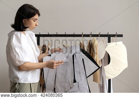 Tailor Or Professional Seamstress Hanging Craft Paper Patterns On Hangers. Concept Of Small Business