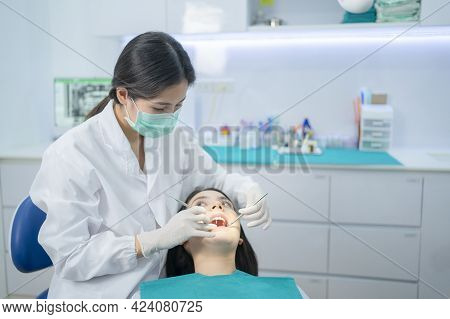 Asian Young Dentist Wearing Face Mask, Using Medical Instruments For Oral Care Check Up. Doctor Exam