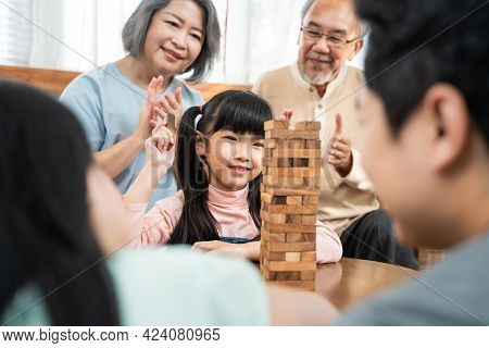 Asian Family Stay Home, Enjoy Activity Relationship In Living Room. Senior Grandparents, Father And