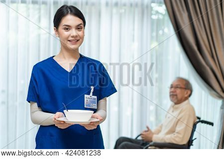 Portrait Of Asian Beautiful Woman Nurse At Nursing Home Hold Food Bowl To Serve Disabled Senior Elde