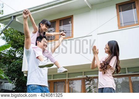 Asian Happy Family Parents With Cute Daughter Outdoor Having Fun Playing The Pilot Of An Airplane At