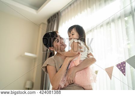 Asian Beautiful Loving Mother Hold Little Baby Girl Daughter In Arm And Spinning Around. Attractive