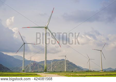 Wind Power Plant. Green Meadow With Wind Turbines Generating Electricity
