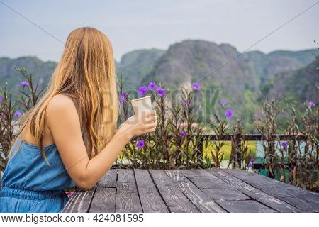 Woman Drinks Coffee In The Morning On The Background Of Hills In Ninh Binh, Tam Coc. Resumption Of T