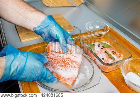 The Process Of Making Lightly Salted Salmon In The Kitchen. Hands In Gloves Hold A Piece Of Fish Spr