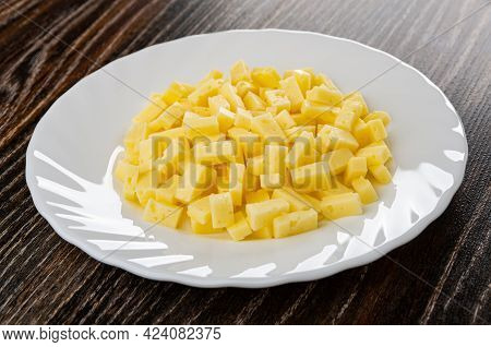 Small Pieces Of Cheese In White Plate On Dark Wooden Plate