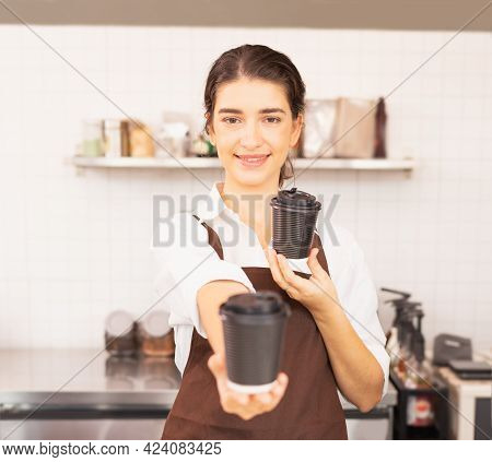 Beautiful Caucasian Barista Woman Happy To Give Takeaway Coffee Cup In One Hand Forward And Shows On