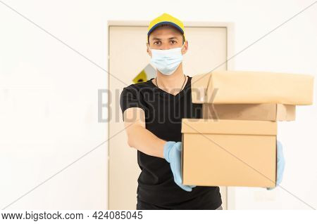 Delivery Man Holding Cardboard Boxes In Medical Rubber Gloves And Mask. Copy Space. Fast And Free De