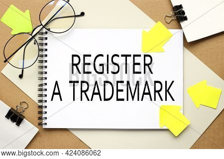 Register A Trademark. Inscription On A Notebook On A Craft And Gray Background