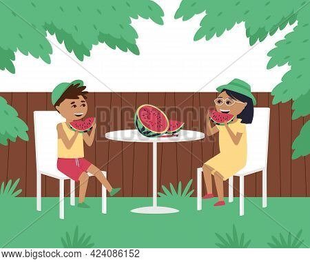 Children Eat Watermelon At A Table In The Yard. In The Summer, Children Wear Caps Outside. Happy Boy