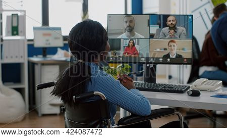 Paralysed Handicapped Black Worker Sitting Immobilized In Wheelchair Having Videomeeting Discussing