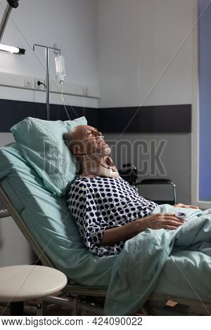 Senior Man Suffering After Serious Accident Laying In Hospital Bed, Wearing Neck Brace. Patient With