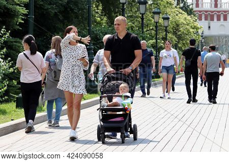 Moscow, Russia - June 2021: Young Couple With Baby Pram Walking On A Street On Crowd Of People Backg