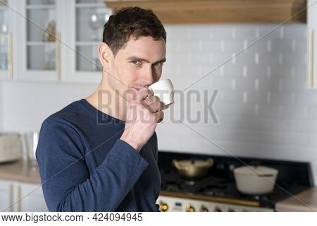 Portrait Of Handsome Young Man, Guy Is Standing At Kitchen In The Morning In Pyjama And Drinking Hot