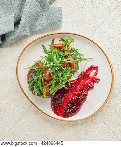 Chopped Veal Steak With Arugula And Cherry Tomato Salad. Served With Wild Berry Sauce. On A White Pl