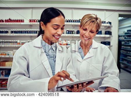 Young Woman Using A Digital Tablet And Showing Something To Her Senior Colleague Wearing Labcoat Whi