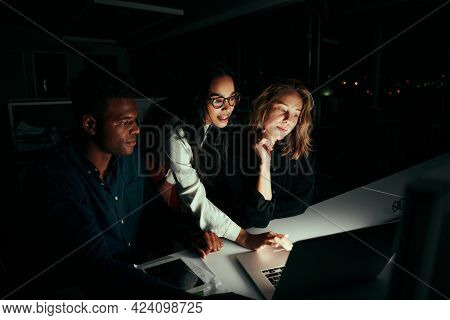 Group Of Diverse Business People Working Overtime In Dark Office Using Laptop