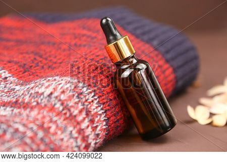 Dropping Essential Oil Into Glass Bottle Or Bottle Of Hyaluronic Acid With Pipette And Autumn Red Kn