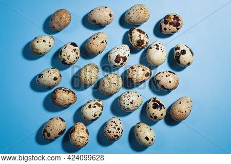 Top View - Quail Eggs On Pastel Blue Background. Minimal Happy Easter Composition. Minimalism Or Hea