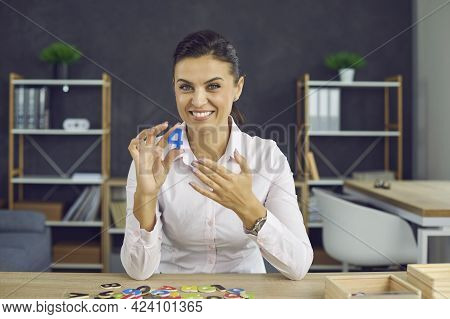 Young Smiling Woman Shows The Number 4. A Young Woman In A White Blouse Of European Appearance
