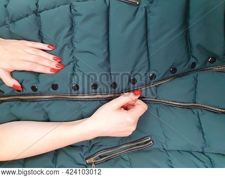 Female Hands With Red Nails Close Zipper Lock On Down Jacket. Autumn Jacket Fabric Background, Green