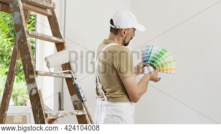 House Painter Man Decorator Choose The Color Using The Sample Swatch, Work The White Wall Of The Hou