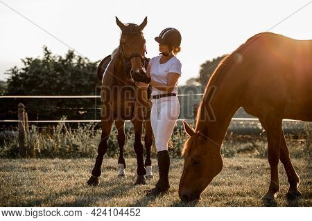 Young Rider Dressed In White Sports Uniform And Helmet, Talking To Her Horse After Training, The Sec